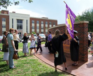 Graduates from Hardin-Simmons University pose for pictures by the Alumni Wall. This is but the surface of the rewards awaiting those who have persevered through college.