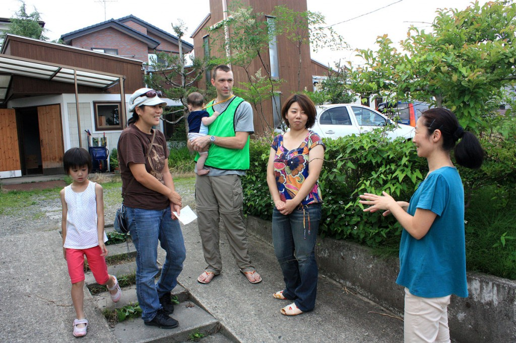 In photo, and Michiko (in hat) and Jonathan Straker (holding son Shiori) talk to neighbors outside the Sendai Church of Christ.